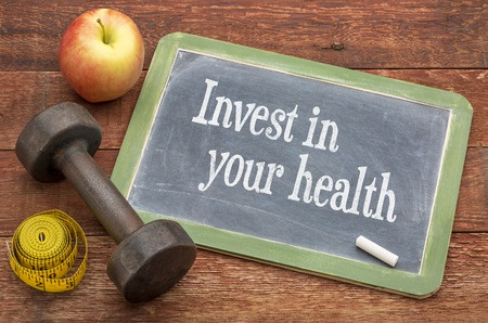 41677071 - invest in your health - slate blackboard sign against weathered red painted barn wood with a dumbbell, apple and tape measure