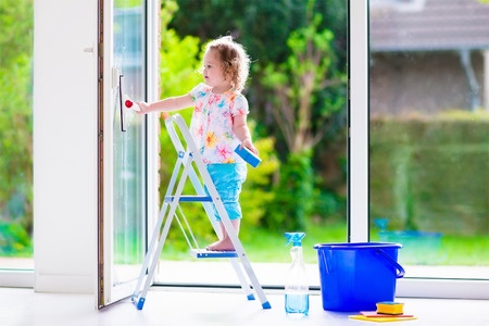 41607896 - little girl washing a window. kids clean the house. children help at home. toddler kid cleaning windows and doors standing on a ladder. child helping with housework holding sponge and soap bottle.